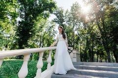 Novia en el vestido blanco del wedd con el ramo a disposición que camina abajo de las escaleras Imagenes de archivo