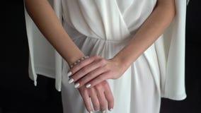 Novia en el vestido blanco puesto en la pulsera en su mano almacen de video