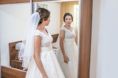 Novia en el vestido blanco que mira en el espejo imágenes de archivo libres de regalías