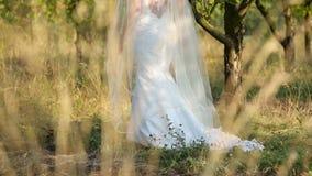 Novia en el vestido de boda blanco que camina en manzanos metrajes