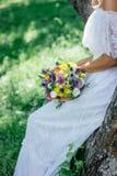 Novia en el vestido de boda blanco que sostiene el ramo de la boda Foto de archivo