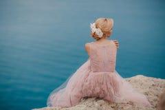 Novia en el vestido de boda que se coloca en una roca Foto de archivo libre de regalías