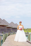 Novia en el vestido de boda que sostiene un manojo de flores fotografía de archivo