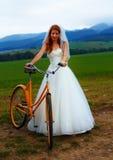 Novia en la bici anaranjada en vestido de boda hermoso con el cordón en paisaje Fotos de archivo libres de regalías
