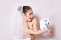 Novia en rotura del velo la foto del novio, fondo gris Fotos de archivo