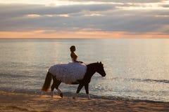 Novia en un caballo en la puesta del sol por el mar Imágenes de archivo libres de regalías