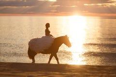 Novia en un caballo en la puesta del sol por el mar Foto de archivo