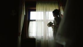 Novia en una estancia de seda blanca de la bata a lo largo de la ventana panorámica en la casa de madera almacen de video