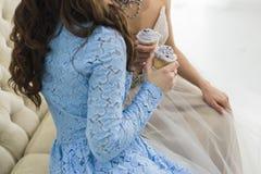 Novia en vestido de boda con la dama de honor sosteniendo las magdalenas azules hermosas Imágenes de archivo libres de regalías
