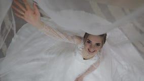 Novia en vestido de boda debajo del velo enorme Mujer bonita y bien arreglada almacen de metraje de vídeo