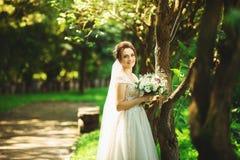 Novia en vestido de boda de la moda en fondo natural Un retrato hermoso de la mujer en el parque foto de archivo libre de regalías