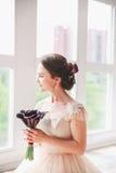 Novia encantadora hermosa en un vestido lujoso que mira para arriba Retrato de la novia feliz que se sienta en vestido de boda en Fotografía de archivo