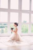 Novia encantadora hermosa en un vestido lujoso que mira para arriba Retrato de la novia feliz que se sienta en vestido de boda en Foto de archivo libre de regalías