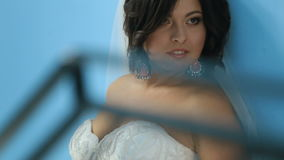 Novia encantadora magnífica en un vestido lujoso que mira para arriba, colocándose cerca de la pared azul Chica joven sensual her metrajes