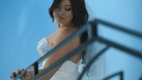 Novia encantadora magnífica en un vestido lujoso que mira para arriba, colocándose en las escaleras Chica joven sensual hermosa e almacen de video