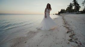 Novia encantadora y feliz en un vestido blanco que baila descalzo en la orilla arenosa de una playa tropical Océano Las palmas almacen de video