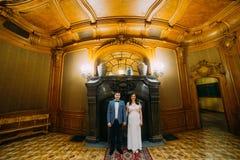 Novia encantadora y novio elegante en la presentación interior clásica del vintage lujoso delante de la chimenea Imagen de archivo libre de regalías