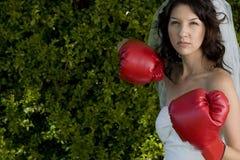 Novia enojada en un vestido de boda y guantes de boxeo Fotos de archivo libres de regalías