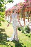 Novia exótica Vestido costoso atractivo atractivo de la muchacha La señora en equipo de lujo camina fondo exótico del jardín La m Foto de archivo