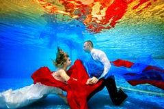 Novia fabulosa y submarino de la nadada y de la danza del novio en la piscina con la tela roja y azul en la puesta del sol Retrat fotos de archivo libres de regalías