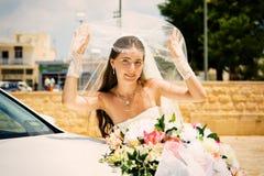 Novia feliz con el ramo cerca del coche de la boda Foto de archivo