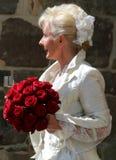 Novia feliz con el ramo de la novia de rosas rojas y de peinado nupcial hermoso en chaqueta romántica del diseñador con un vidrio imágenes de archivo libres de regalías