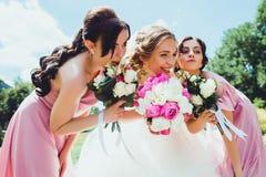 Novia feliz con las damas de honor en el parque en el día de boda Foto de archivo
