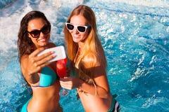 Novia feliz con una bebida en un partido del verano por la toma de la piscina fotografía de archivo libre de regalías