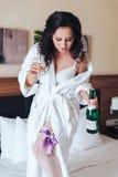Novia feliz con una botella y un vidrio de champán en la cama, peinado moreno del maquillaje Imagen de archivo