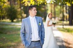Novia feliz, novio que se coloca en parque verde, besándose, sonriendo, riendo amantes en día de boda Pares jovenes felices en am Foto de archivo libre de regalías
