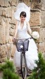 Novia feliz que monta una bici Imagen de archivo libre de regalías