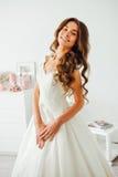 Novia feliz que sonríe en la cámara El peinado de la boda y compone Fotos de archivo