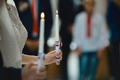Novia feliz y novio elegante que llevan a cabo la ceremonia de boda de las velas, par de la boda en el matrimonio en iglesia, mom foto de archivo
