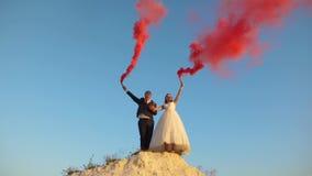 Novia feliz y novio que agitan humo rosado coloreado contra el cielo azul y la risa honeymoon romance relación en medio imágenes de archivo libres de regalías