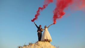 Novia feliz y novio que agitan humo rosado coloreado contra el cielo azul y la risa honeymoon romance relación en medio foto de archivo