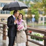Novia feliz y novio que ocultan de la lluvia Fotos de archivo