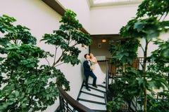Novia feliz y novio que presentan en las escaleras que miran para arriba Hojas de la planta verde en un primero plano Imagen de archivo