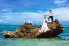 Novia feliz y novio que se divierten en una playa tropical bajo p Imágenes de archivo libres de regalías