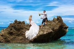 Novia feliz y novio que se divierten en una playa tropical bajo p Imagen de archivo libre de regalías