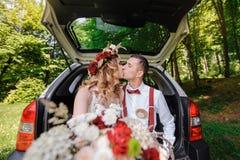 Novia feliz y novio que se sientan en el tronco de un coche Foto de archivo