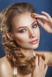 Novia hermosa con el peinado de la boda de la moda - en fondo azul Fotos de archivo