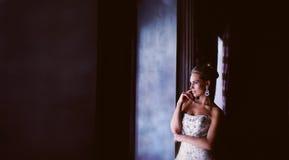 Novia hermosa con un perfil que mira hacia fuera la ventana Imágenes de archivo libres de regalías