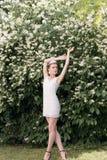 Novia hermosa de la muchacha en un vestido blanco corto con una corona de flores en el jardín que camina entre los árboles del ja Foto de archivo libre de regalías