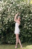 Novia hermosa de la muchacha en un vestido blanco corto con una corona de flores en el jardín que camina entre los árboles del ja Foto de archivo