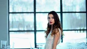 Novia hermosa delante de la cámara, vestido del diseñador, pendientes, mirada sensual de la muchacha almacen de metraje de vídeo