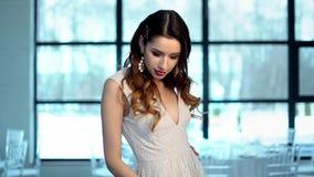 Novia hermosa delante de la c?mara, vestido del dise?ador, pendientes, mirada sensual de la muchacha almacen de video