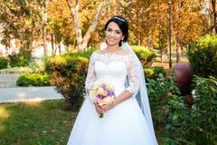 Novia hermosa en día de boda en el fondo del bosque del otoño con un ramo hermoso Fotos de archivo