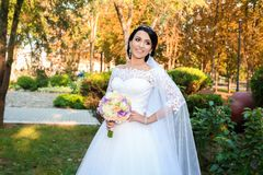 Novia hermosa en día de boda en el fondo del bosque del otoño con un ramo hermoso Fotos de archivo libres de regalías