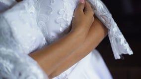 Novia hermosa en la bata de casa blanca de la boda que sostiene y que abraza el vestido de boda almacen de metraje de vídeo