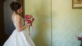 Novia hermosa en la bata de casa blanca de la boda que sostiene y que abraza el vestido de boda almacen de video